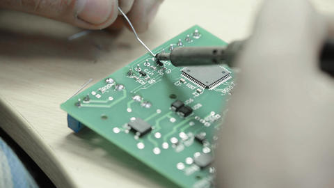 A worker is working on the creation of an electronic board. Close-up Live Action