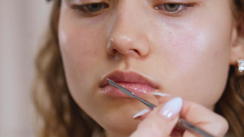 Preparing the model's skin for applying makeup. Lip treatment with a spatula and lip balm. Close up Live Action