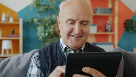 Elderly man touching tablet screen relaxing on couch in apartment using gadget Live Action