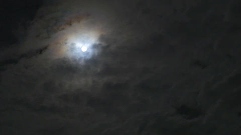 Time lapse of the moon glowing behind the clouds Footage