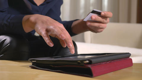 Close-up of a young businesswoman paying bills and using online banking on a tab Footage