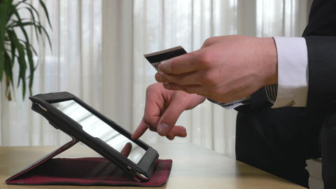 Young businessman using online banking on a tablet pc Footage