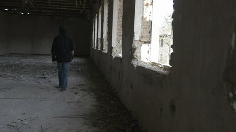 Hooded sad young man walking in an abandoned military building Footage