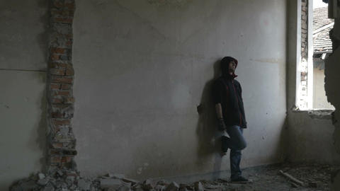 Hooded depressed young man sitting in an abandoned building Footage
