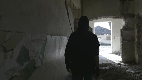 Hooded young man walking through the hallway of an abandoned building Footage