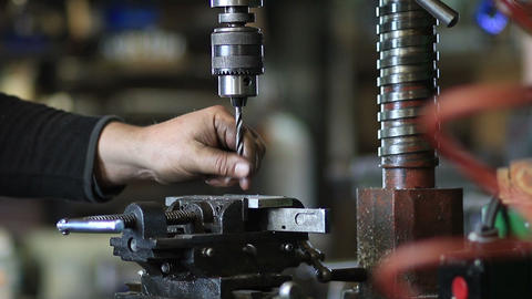 Drilling hole in iron piece with auger in workshop Footage