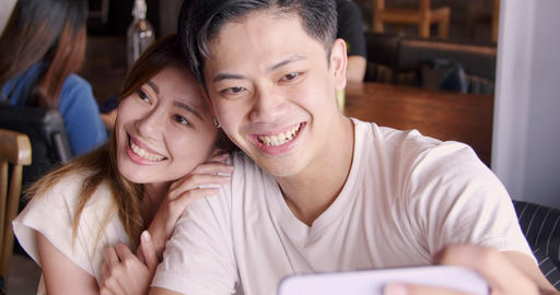 happy young couple taking selfie with cellphone camera in restaurant Live Action