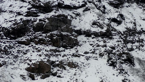 AERIAL: Snow White Mountain with Black Rocks in Iceland Winter, Snowing, Cold Live Action
