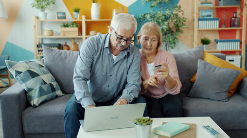 Elderly husband and wife making money transaction with bank card and laptop at Live Action