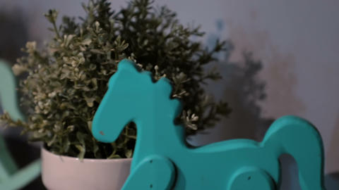 Miniature wooden rocking horse toy and a flowerpot on a wooden shelf Live Action