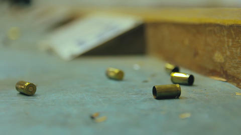 Empty pistol bullet shells dropping and impacting wooden table in a shooting range Live Action