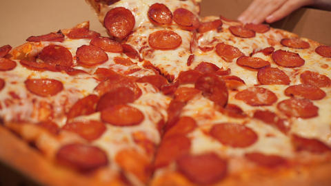 Close up hands taking sliced hot pepperoni pizza. People hands taking pizza ライブ動画