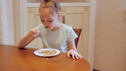 Unhappy girl teenager eating buckwheat porridge while fitness diet. Sad girl Live Action