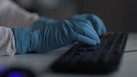 Laboratory assistant in gloves is typing result of research on a computer Live Action