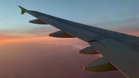 A large air plane on a cloudy day, wing of plane at sunset or sunrise, blue sky Live Action