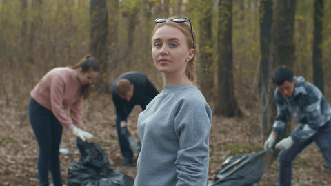 Woman with trash bag and people collecting garbage on background Live Action