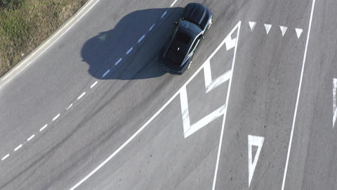Top view black sedan car driving on asphalt circular road with marking. Aerial view from drone sport Live影片