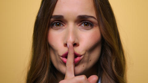 Business woman putting finger on mouth. Girl keeping secret with finger on lips Live Action