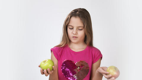 Girl with an Apple. little girl holds an Apple in her hand and looks at the Live Action