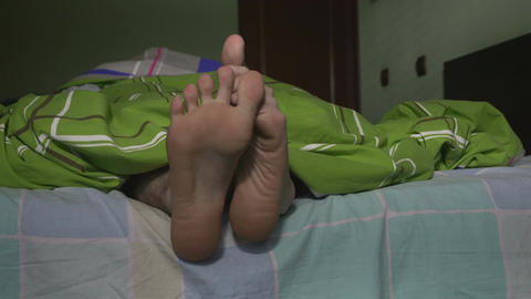 Close-up of male feet playing in bed Footage