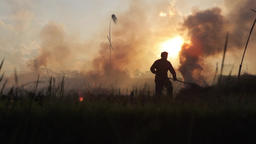 Silhouettes of farmer working and woman passing by in the smoke of stubble burni Footage