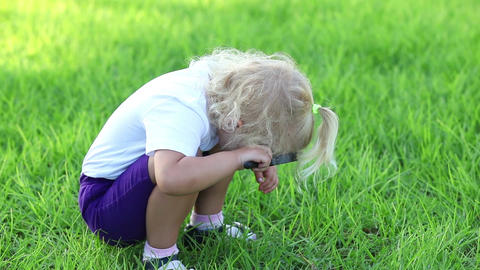 Little girl sitting on the grass and looks through a magnifying glass Footage