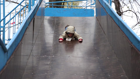 Boy rides on a sliding board Footage
