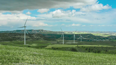 Beautiful green field with wind turbines rotating. Renewable energy source Live Action
