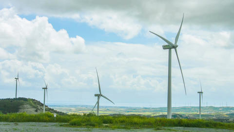 Windmill propellers spinning. Green energy generation. Clouds in stormy sky Footage