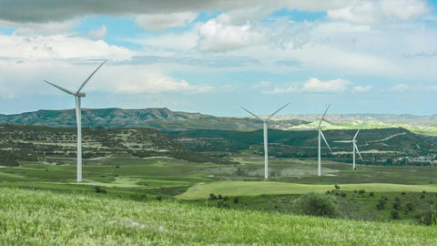 Amazing panorama of green field with spinning windmills, mountains on horizon Footage
