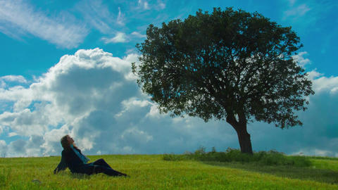 Lonely woman sitting under green tree, enjoying sunny windy weather, thinking Footage