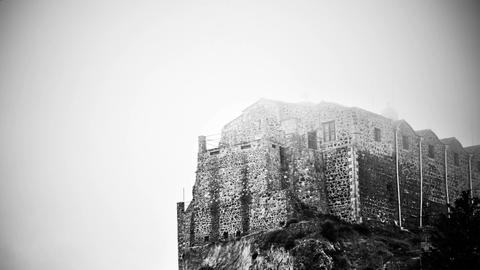 Black and white mysterious haunted castle standing on foggy top of mountain Footage