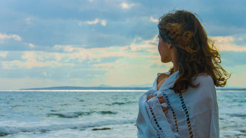 Lonely beautiful woman covered with scarf standing near sea, looking at storm Footage