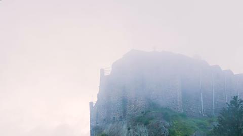 Old Orthodox monastery on mountain peak. Misty stone building standing on hill Footage