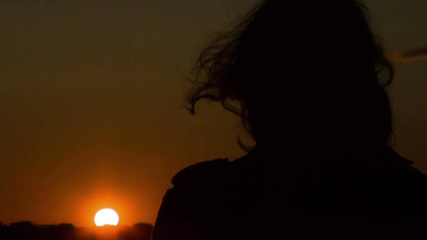 Dark silhouette of woman looking at sunset, wind waving her hair. Changes Footage