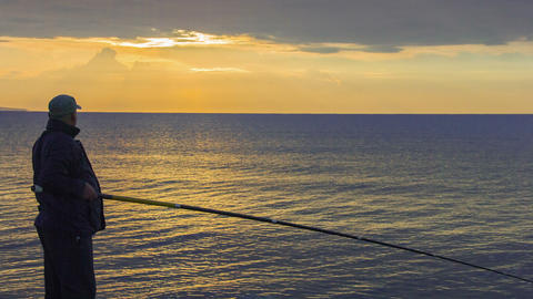 Man fishing at sunrise, enjoying hobby, spending his leisure time with pleasure Footage