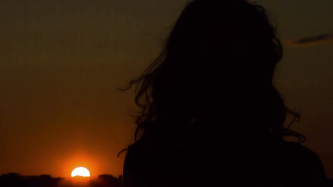 Lonely young woman looking at sunset, thinking, wind playing with her hair Footage
