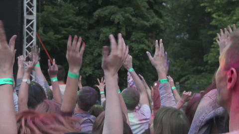 Young men and women enjoying traditional paint fest, jumping with hands in air Footage