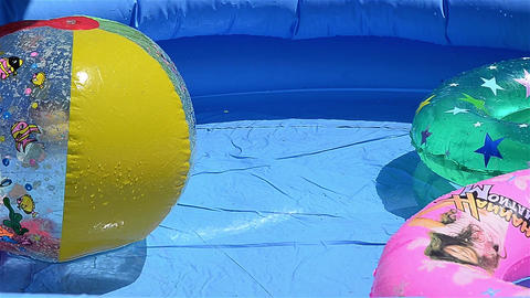 Ball plastic and rubber toys floating in a pool of blue clear water Footage