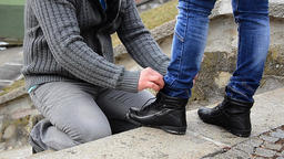 Man knotted laces on black shoes of his girlfriend Footage