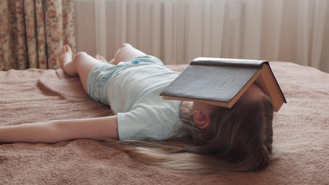 Face sleeping girl covered opened book in home bedroom. Young girl lying on bed Live Action