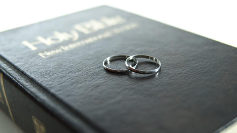 Two silver wedding rings on bible cover GIF
