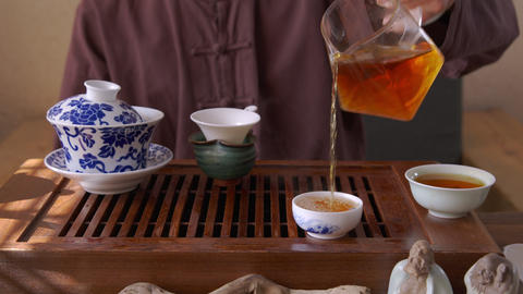 Male hand pouring hot red tea from glass pot in bowl on traditional ceremony GIF