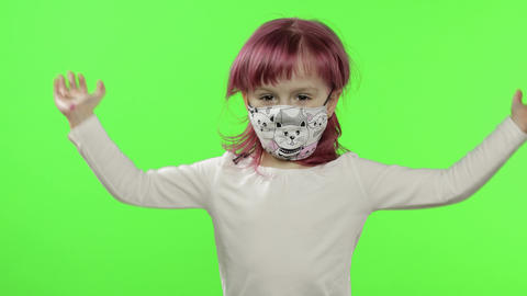 Little girl in medical face mask. Grabs her head in fear. COVID-19 coronavirus Live Action
