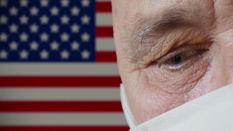 Half face of an elderly man in protective mask USA flag background Live Action