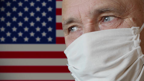 Elderly man in handmade protective mask USA flag background Live Action