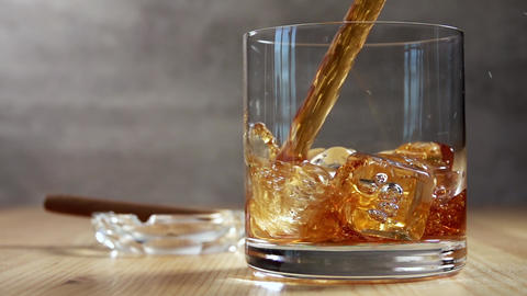 Pouring Whiskey into a Glass With Ice. Slow Motion Live Action