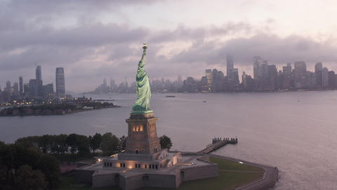 AERIAL: Circling Statue of Liberty illuminated in early morning light with foggy Live Action
