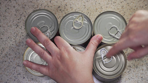 Canning supplies concept with counting food cans female hand top view Live Action
