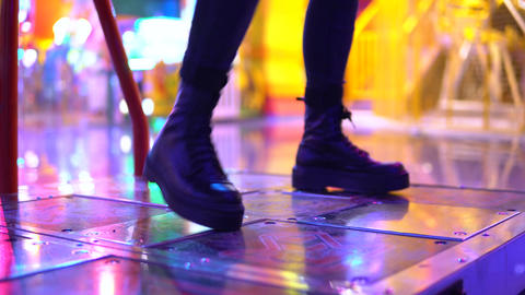 A young woman plays dancing in an amusement park. A girl plays with her legs in Live Action
